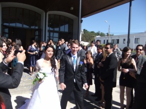 Mark and Carolina making their way out through the rose pedals flying through the air.